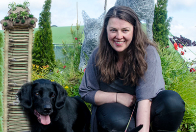 woman kneeling down with black dog in garden