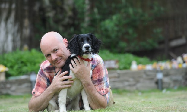 man cuddles dog in garden