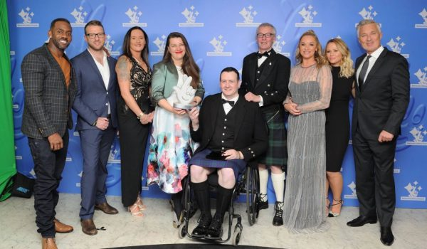 five men and four women at an awards ceremony. one man in a wheel-chair