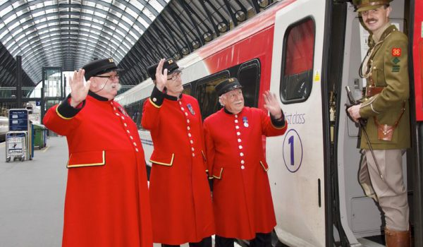three chelsea pensioners and WWI army officer at train station