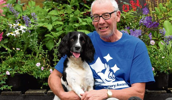 middle aged man cuddles dog in garden