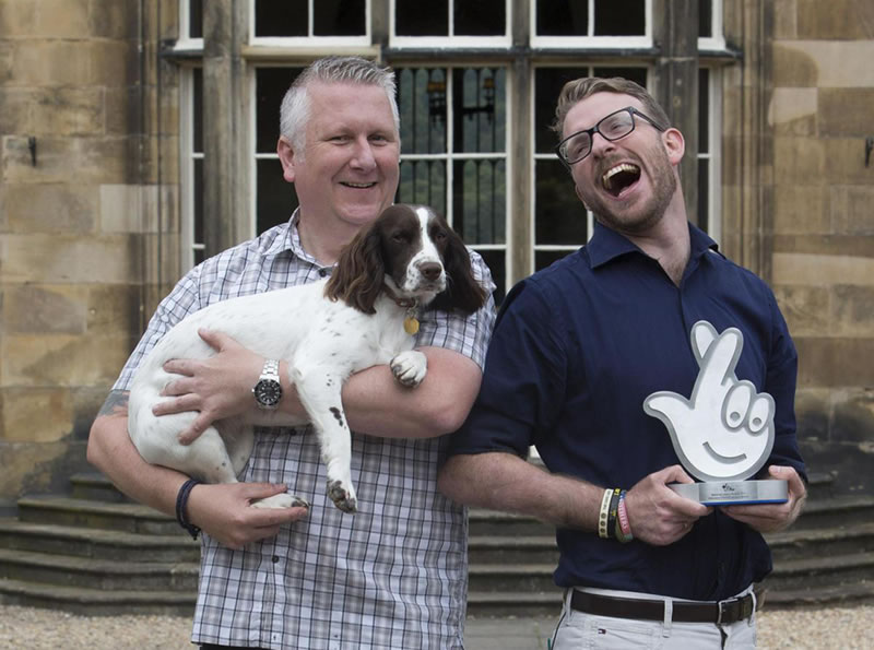 Two men with one holding a dog and national lottery award