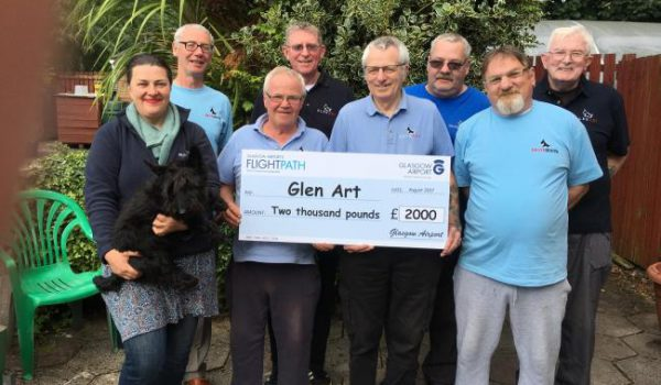 six old men and a woman holding dog hold cheque for 2000 pounds