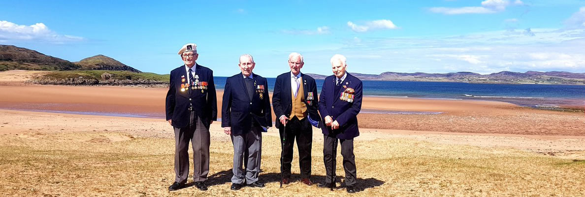 four WWII veterans with medals stand on a beach