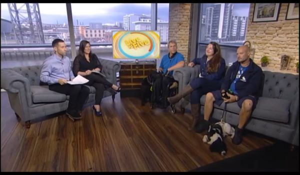 three men, two women and a dog in TV studio