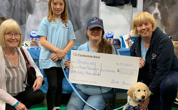 group of people present cheque to brave hound charity